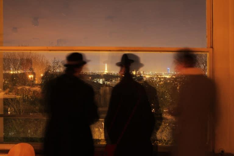 trois ombres devant une fenetre vue sur Paris