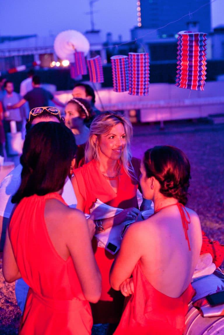 femmes glamour en robe rouge pendant une soiree rooftop a paris