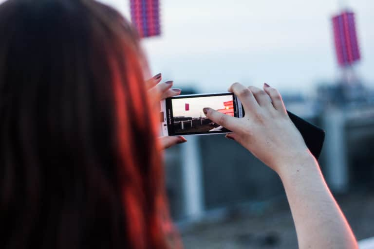 girl taking picture of a rootop view with sony xperia phone in paris