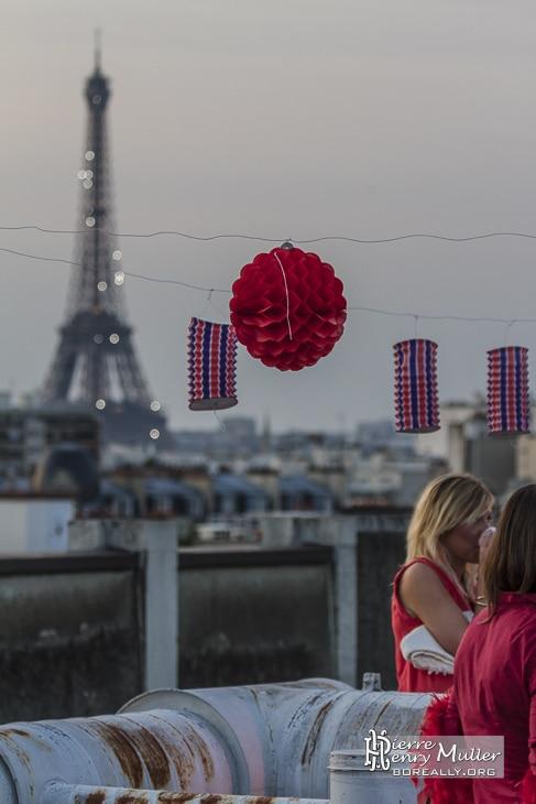 tour eiffel lampion tricolore femme blonde robe rouge soiree 14 juillet rooftop paris