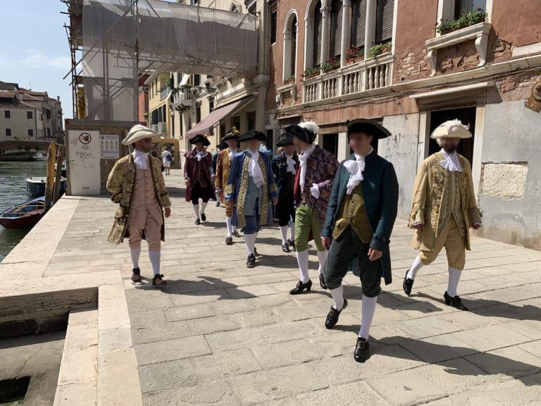 seminaire-venise-hommes-costumes-sur-un-quai-au-bord-de-canal