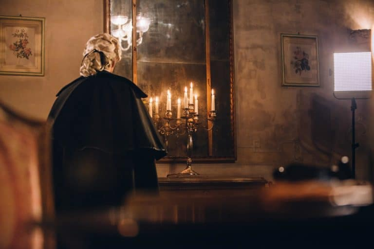 personnage mysterieux costume venitien de dos miroir chandelier