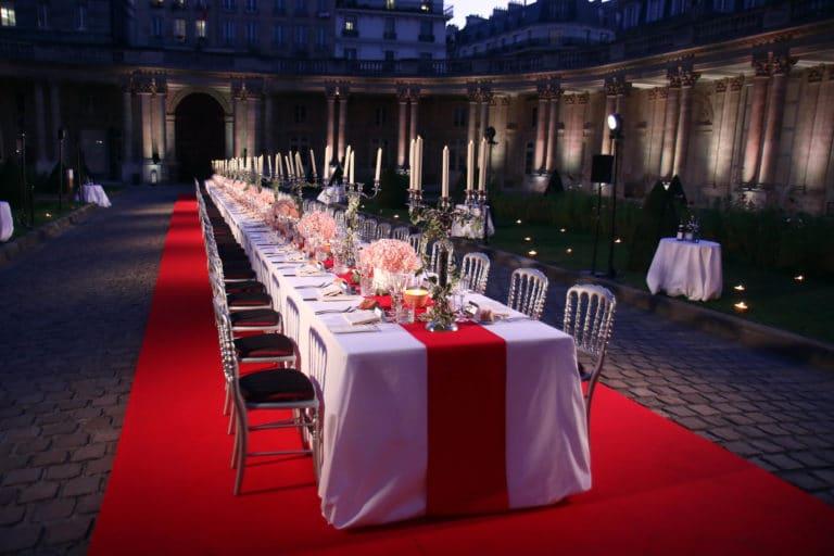 Diner d exception paris luxe chandeliers fleurs table nappe rouge et blanche cour d honneur hotel de soubise paris evenementiel agence WATO paris